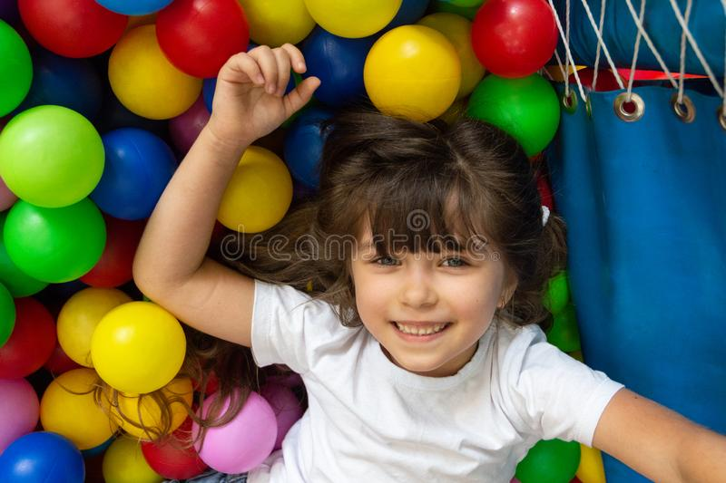 Child playing with colorful balls in playground ball pool. Activity toys for little kid. Kids happiness emotion having fun in ball royalty free stock photography