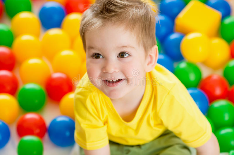 Child playing colorful balls top view royalty free stock photography