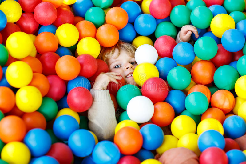 Child playing at colorful plastic balls playground stock photo