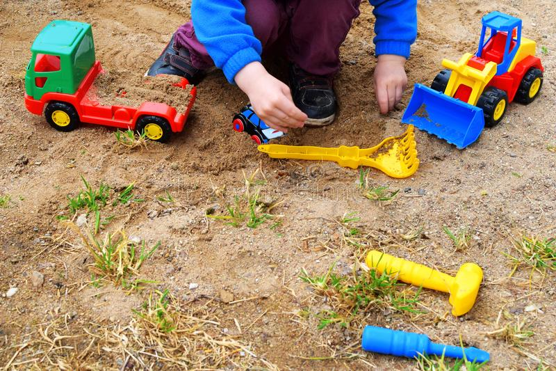 Child playing with colorful toy cars. Little child hands playing with colorful plastic toy cars in sand outdoors royalty free stock photos