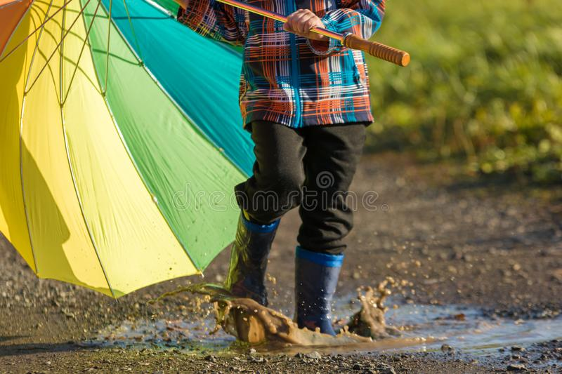 Child is playing with colorful umbrella in a puddle stock photography