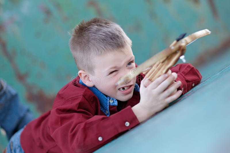 Child playing with crossbow. Portrait of cure young boy playing with cross bow toy or weapon on floor stock photos