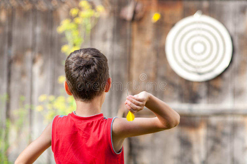 Child playing darts. Young boy playing darts outdoor stock images