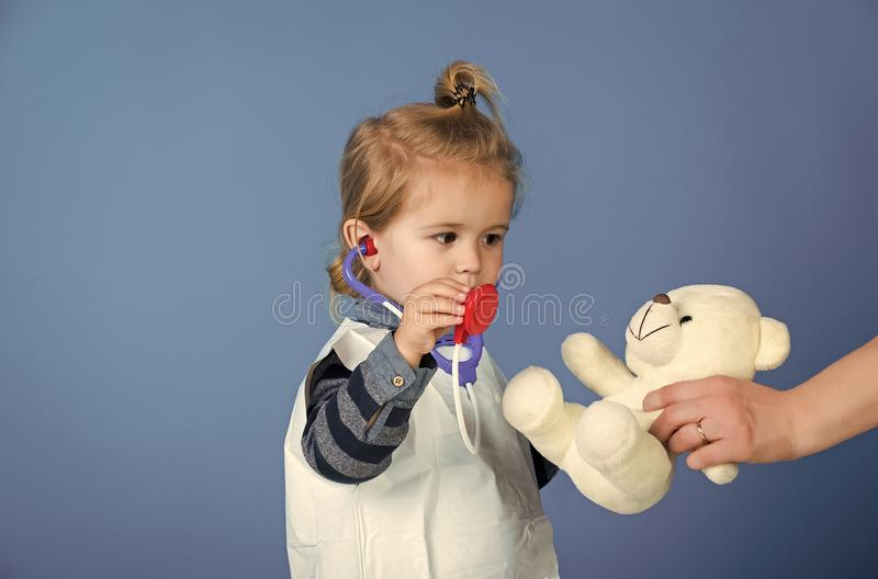 Child is playing doctor. Child play veterinarian with teddy bear in mothers hand. Boy doctor examine toy pet with stethoscope on blue background. Future royalty free stock images