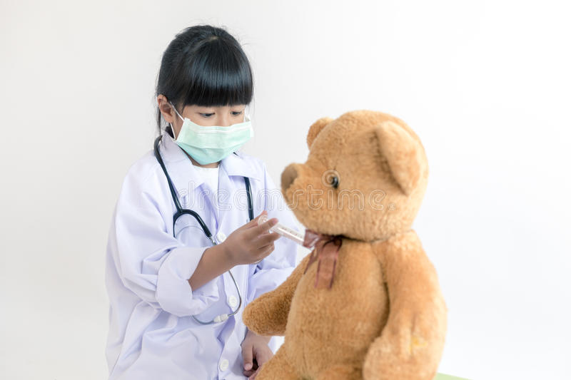 Child playing doctor with stethoscope and teddy bear stock images