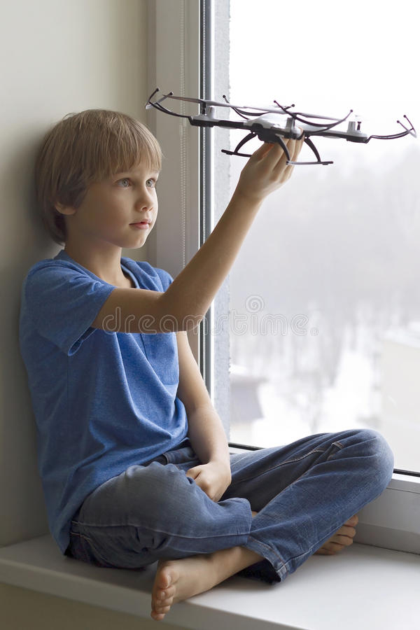 Child playing with drone. Boy sitting on window sill and holding quadrocopter in his hand. Technology, leisure toys royalty free stock photos