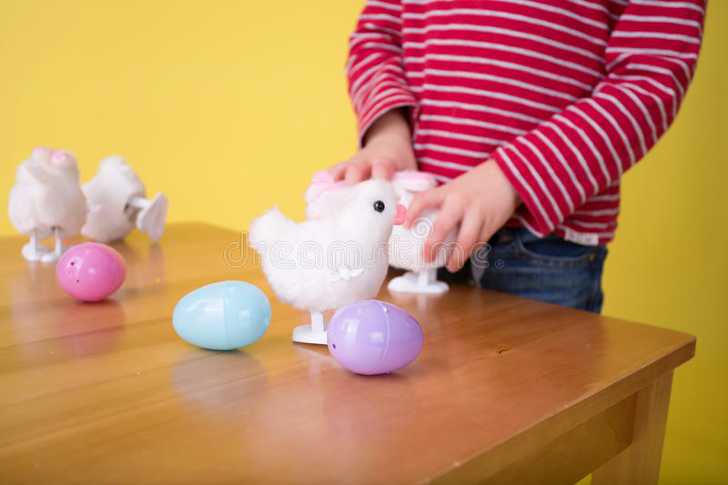 Child playing with Easter Bunny Toys. Child having fun and playing with wound up easter bunny toys stock photos