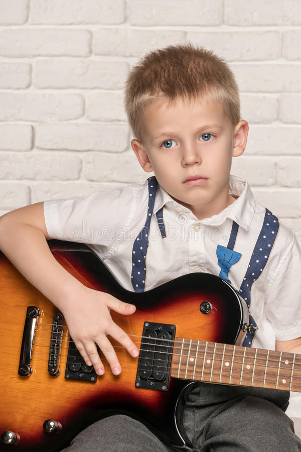 Child playing on electric guitar. Little beautiful boy playing on electric guitar sitting on a chair near brick wall royalty free stock photography