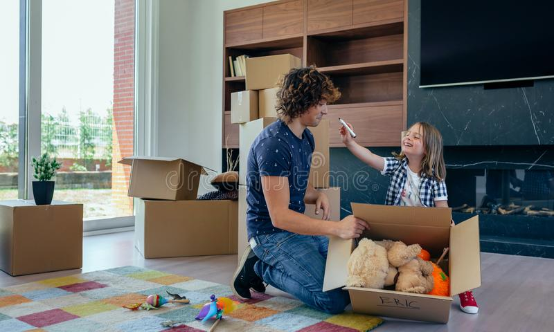 Child playing with father preparing moving boxes stock images