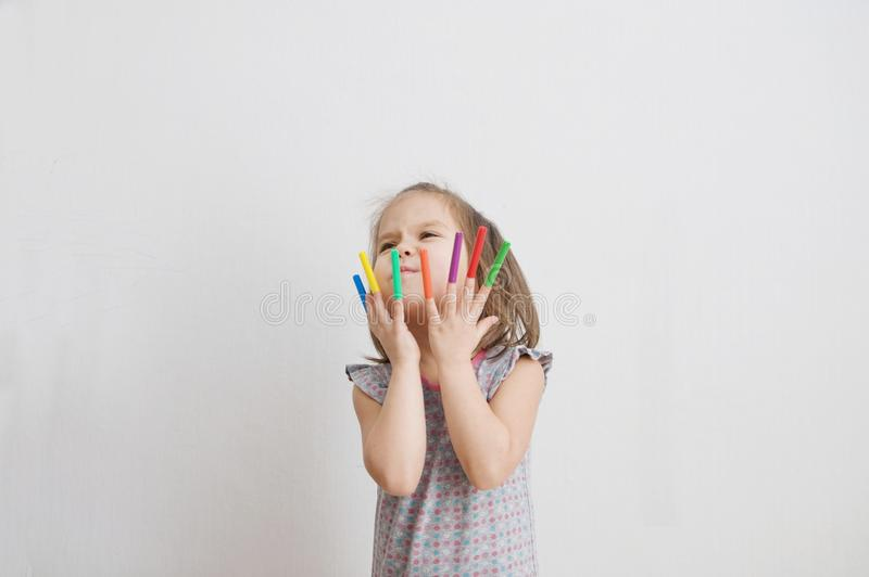 Child playing with felt tip pens stuff. baby girl painting and playing. colorful felt pen caps on fingers. Of kid stock image