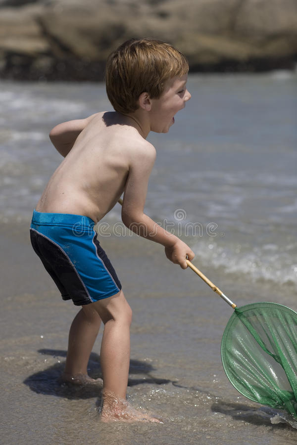 Child playing with a fishing net. stock image