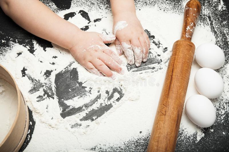 A child is playing with flour in the kitchen stock photo