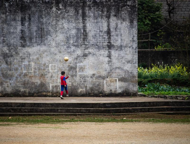 Child playing football against a wall royalty free stock image