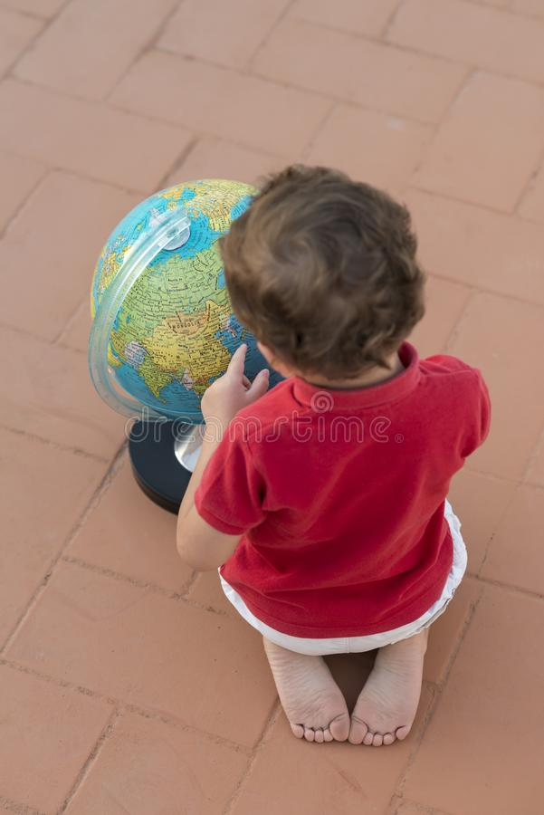 Child playing with a globe. Color photography of a child playing with a globe royalty free stock images