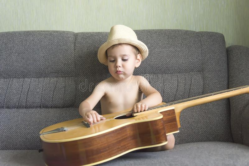 Child playing the guitar stock photo