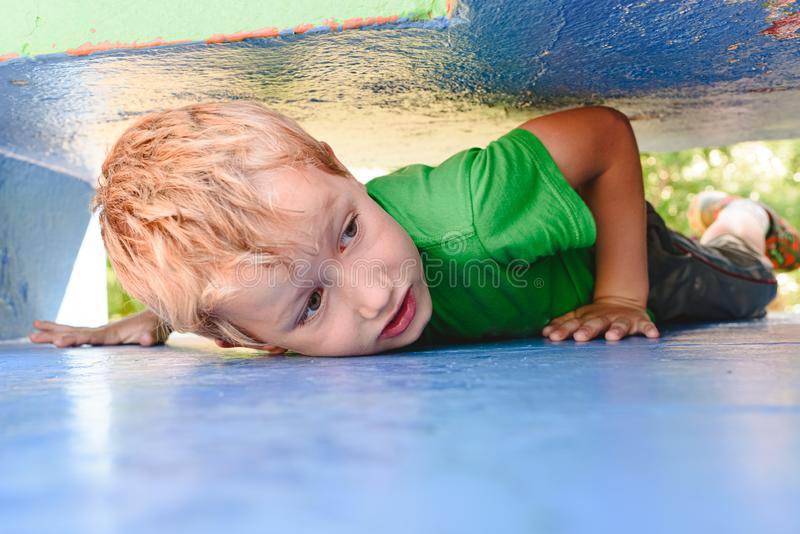 Child playing hide and seek in an urban concrete maze looking for fun for his friends royalty free stock photos