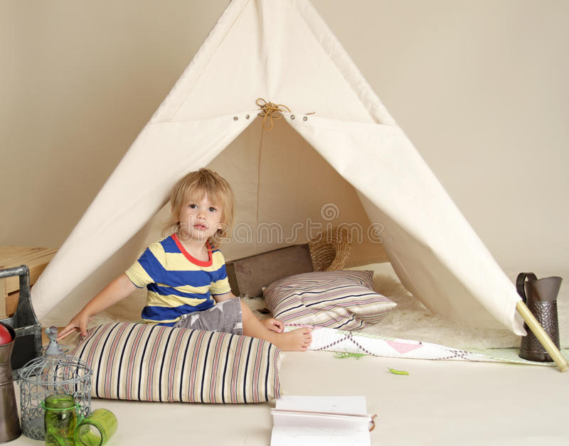 Child Playing Indoors with Teepee Tent. Child playing at home indoors with a teepee tent stock photos