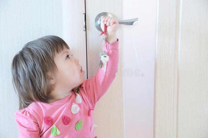 Child playing with keys forgotten by parents in door keyhole. Children safety and home safety royalty free stock photo