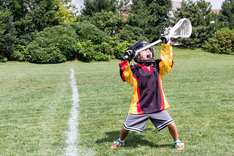 Child playing lacrosse screams in celebration joy while holding. Child playing lacrosse screams for joy while holding stick over head stock photography