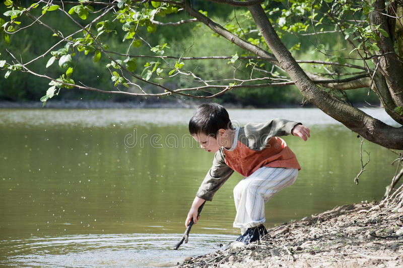 Download Child playing by the lake stock photo. Image of trees - 24719832