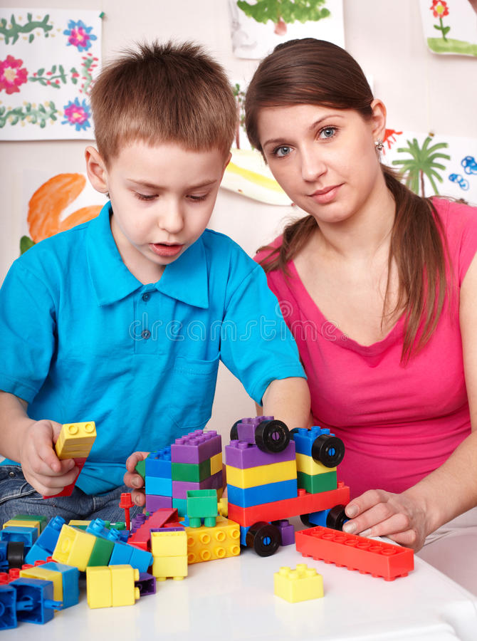 Child playing lego block with mother at home. royalty free stock images