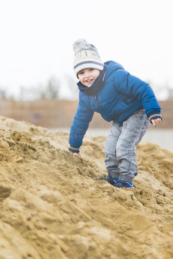 Child playing with a log on the beach. In winter royalty free stock photo