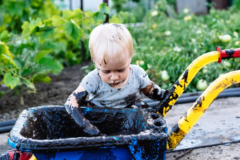Child playing in the mud on the street stock photo