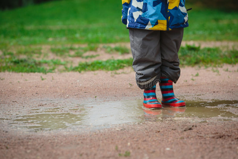 Child playing in muddy puddle royalty free stock photography