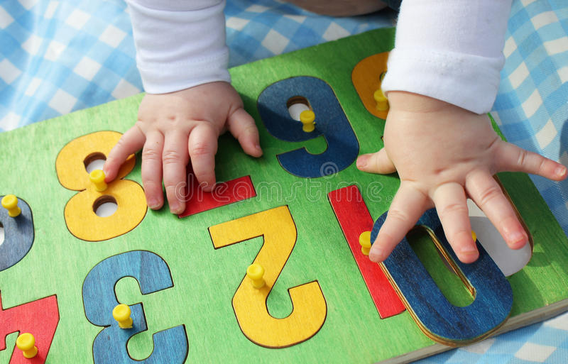 Child playing with a number puzzle royalty free stock image