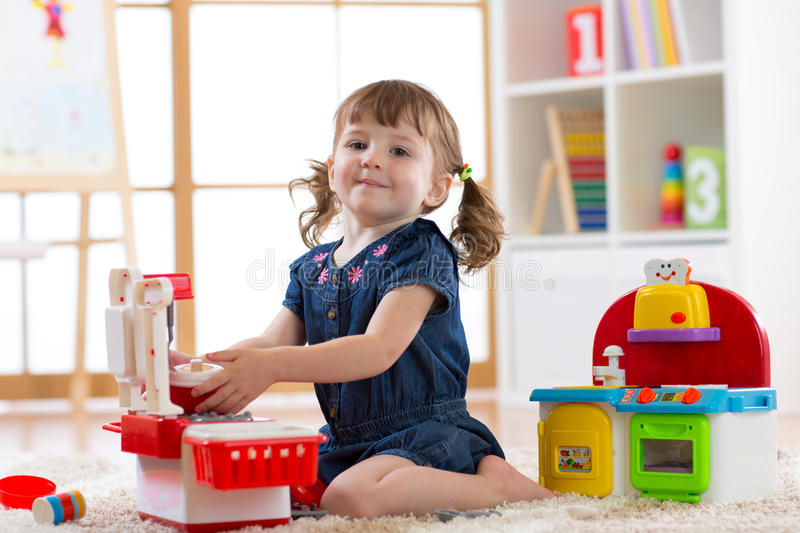 Child playing in nursery with educational toys. Toddler kid in a playroom. Little girl cooking in toy kitchen. stock images