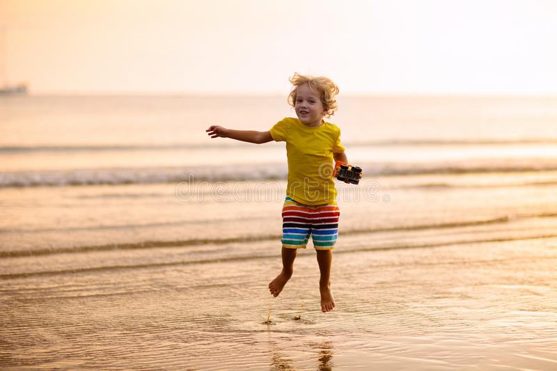 Child playing on ocean beach. Kid at sunset sea royalty free stock photography