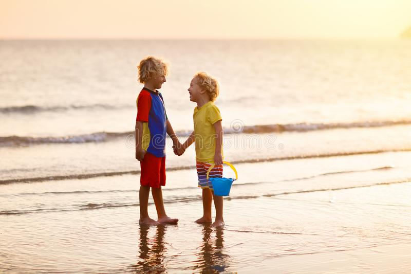 Child playing on ocean beach. Kid at sunset sea royalty free stock photos