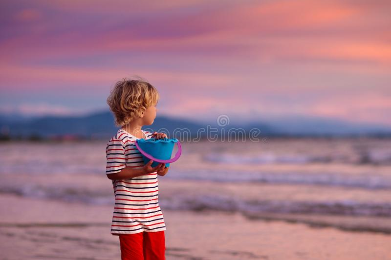 Child playing on ocean beach. Kid at sunset sea royalty free stock photo