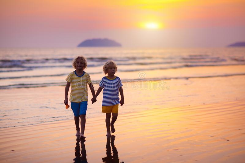 Child playing on ocean beach. Kid at sunset sea stock photos