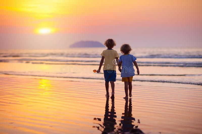 Child playing on ocean beach. Kid at sunset sea royalty free stock images