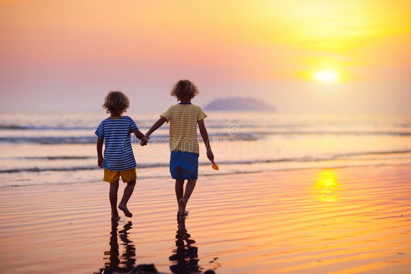 Child playing on ocean beach. Kid at sunset sea stock image