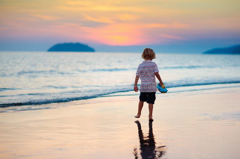 Child playing on ocean beach. Kid at sunset sea stock photography