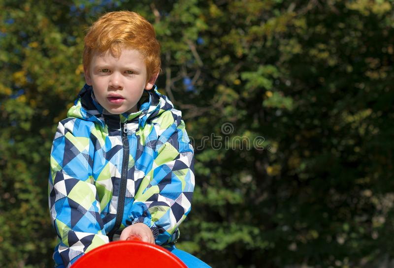 Child playing on outdoor playground. Boy play on school or kindergarten yard. Kid with curly ginger hair. Portrait. The royalty free stock photography