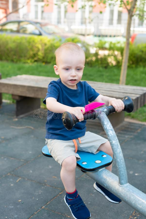 Child playing on outdoor playground in summer. Kids play on kindergarten yard. Active kid on colorful swing. Healthy. Child playing on outdoor playground in stock photography