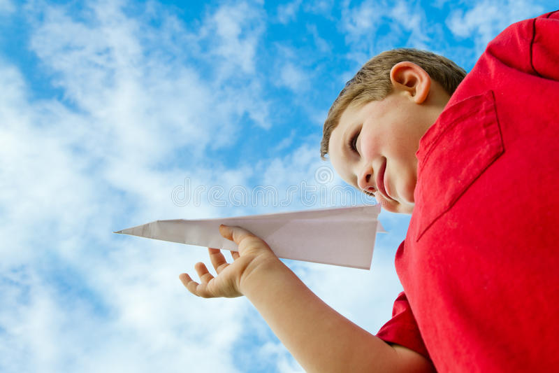 Child playing with paper airplane. Under cloudy blue sky stock photos