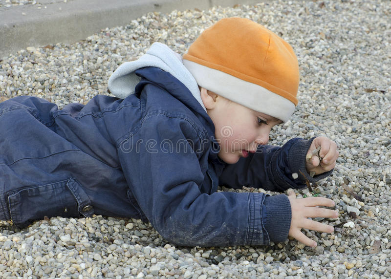 Child playing with pebbles royalty free stock image