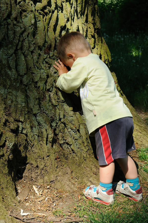 Child playing peek-a-boo. Little child playing peek-a-boo, hiding his face and counting down royalty free stock image