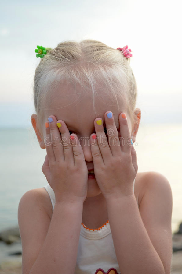 Child is playing peek-a-boo. Little girl is playing peek-a-boo stock photography