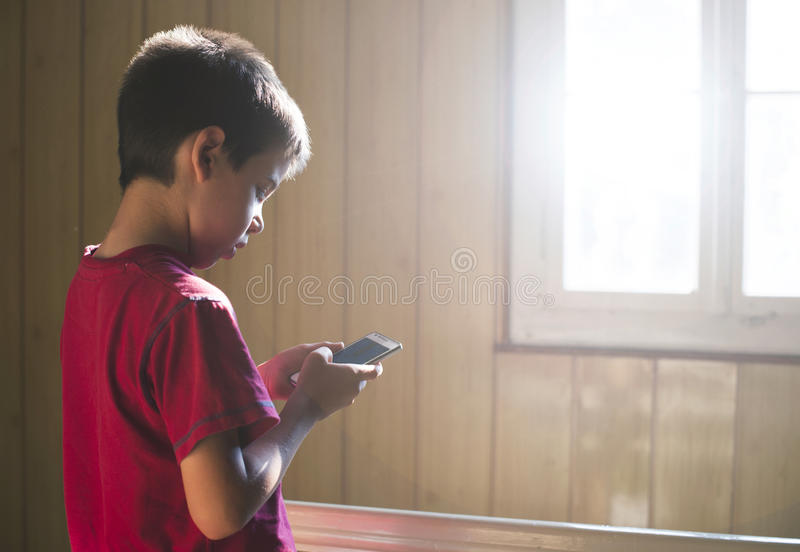 Child playing with phone. Child playing with mobile phone. Sunlight thru the window stock photography