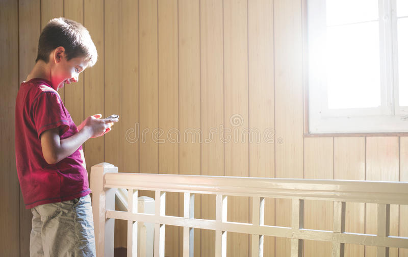 Child playing with phone. Child playing with mobile phone. Sunlight thru the window royalty free stock image