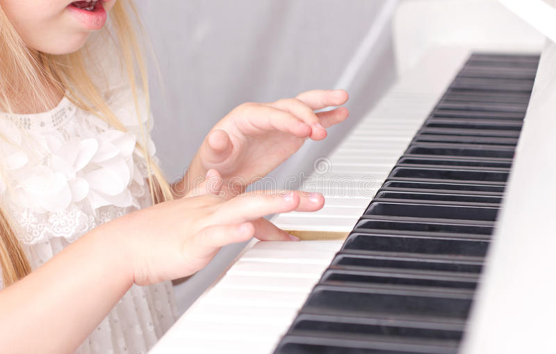 Child playing on piano stock photo