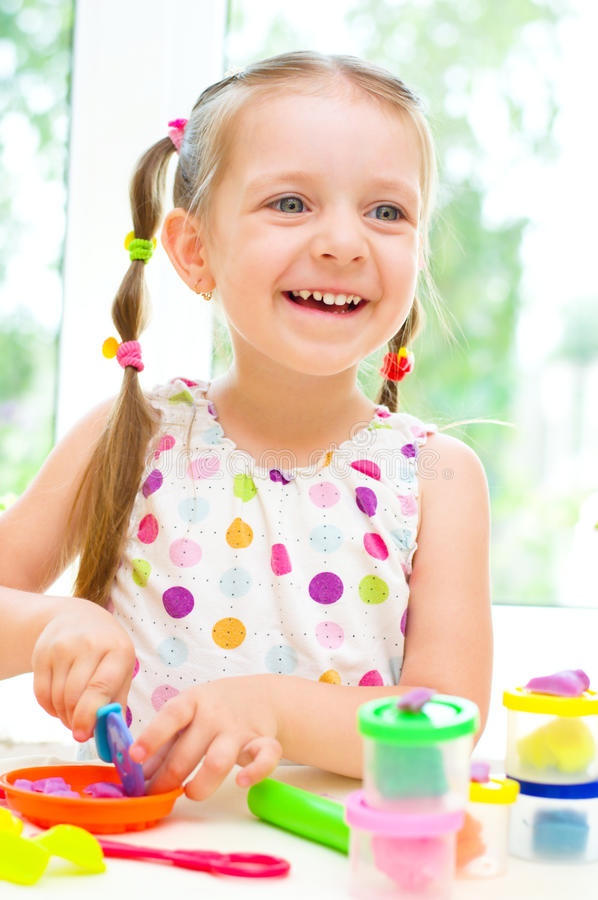 Child Playing with Play Dough. Happy Little Girl Playing with Color Play Dough royalty free stock images