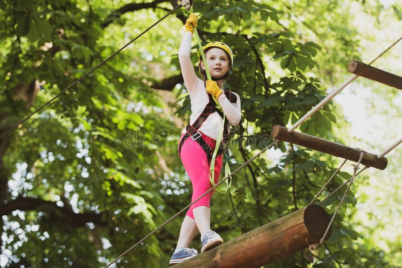 Child playing on the playground. Children fun. Hiking in the rope park girl in safety equipment. High ropes walk. Rope. Park - climbing center royalty free stock photography