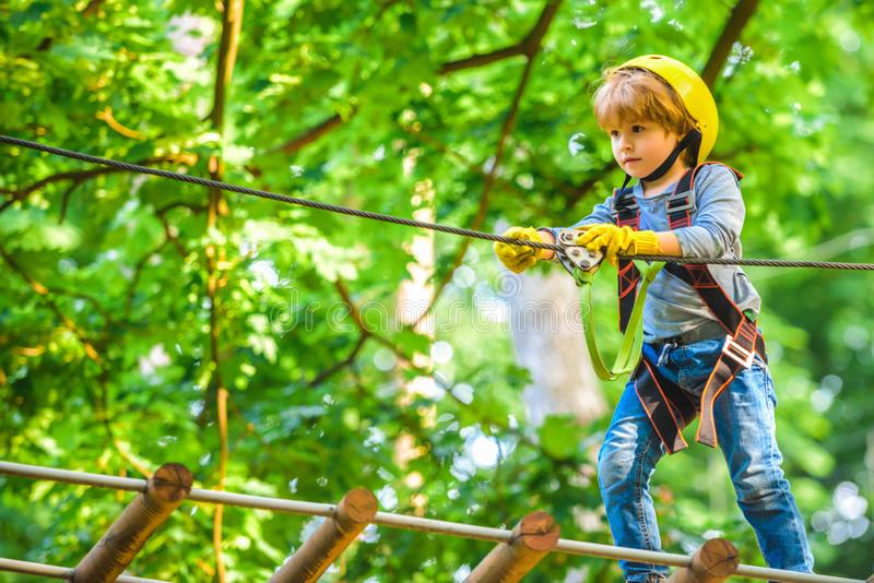 Child playing on the playground. Roping park. Active children. Safe Climbing extreme sport with helmet. Happy Little royalty free stock photo