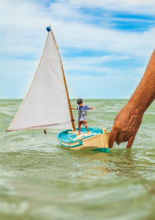 Child playing with pleasure boat on the beach stock images